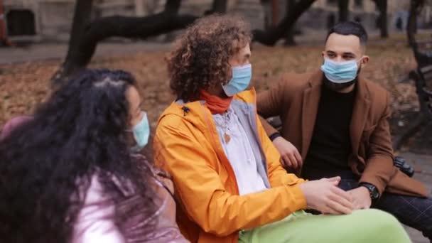 Multikulti-Freunde in Masken sitzen im Park
