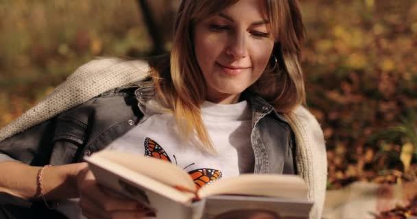 fiatal nő pihentető a parkban, és olvasási könyv
