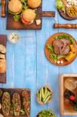Fotografie grilované hamburgery, steaky, plněné cukety, zelenina a omáčky