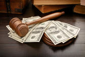 Judge gavel with dollars and law books