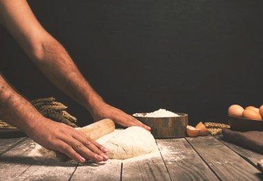 Men hands roll out dough close up