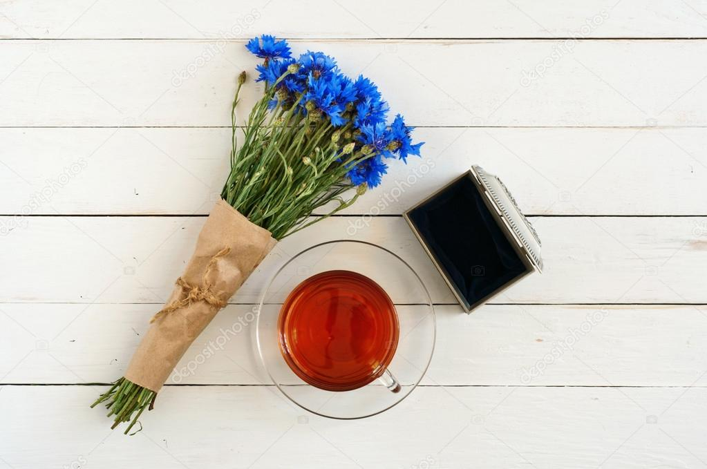 bouquet of flowers on white wooden background with a cup of tea with the old open box