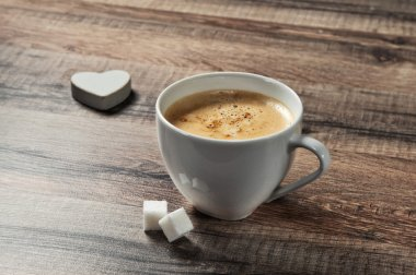 cup of espresso coffee on a wooden table with sugar and wooden heart closeup