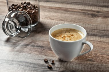 cup of coffee on a wooden table with coffee beans closeup