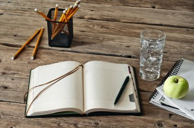 blank diary on wooden table with a glass of water, apple and pencil closeup
