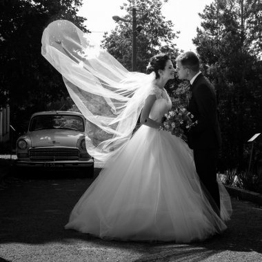 bride and groom kissing in park