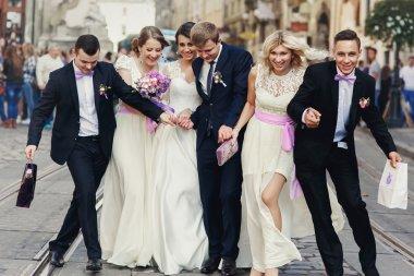 Happy fun newlyweds posing in street