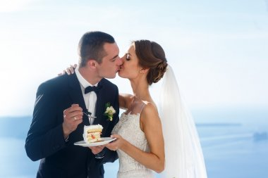 Happy bride and groom eating cake