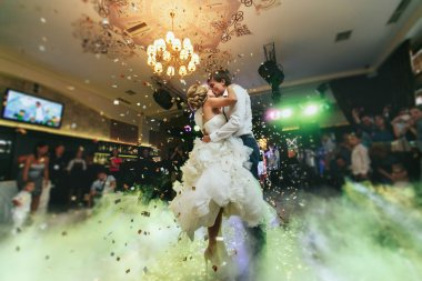 Happy stylish newlyweds dancing