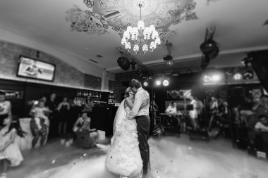 Happy stylish newlyweds kissing at reception