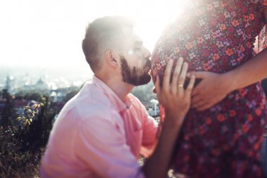 happy man kissing wife's pregnant belly