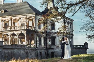 Beautiful fairytale newlywed couple hugging