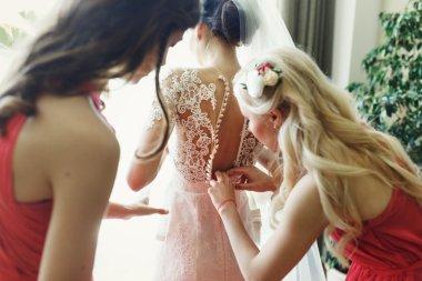 Bride getting prepared with bridesmaids