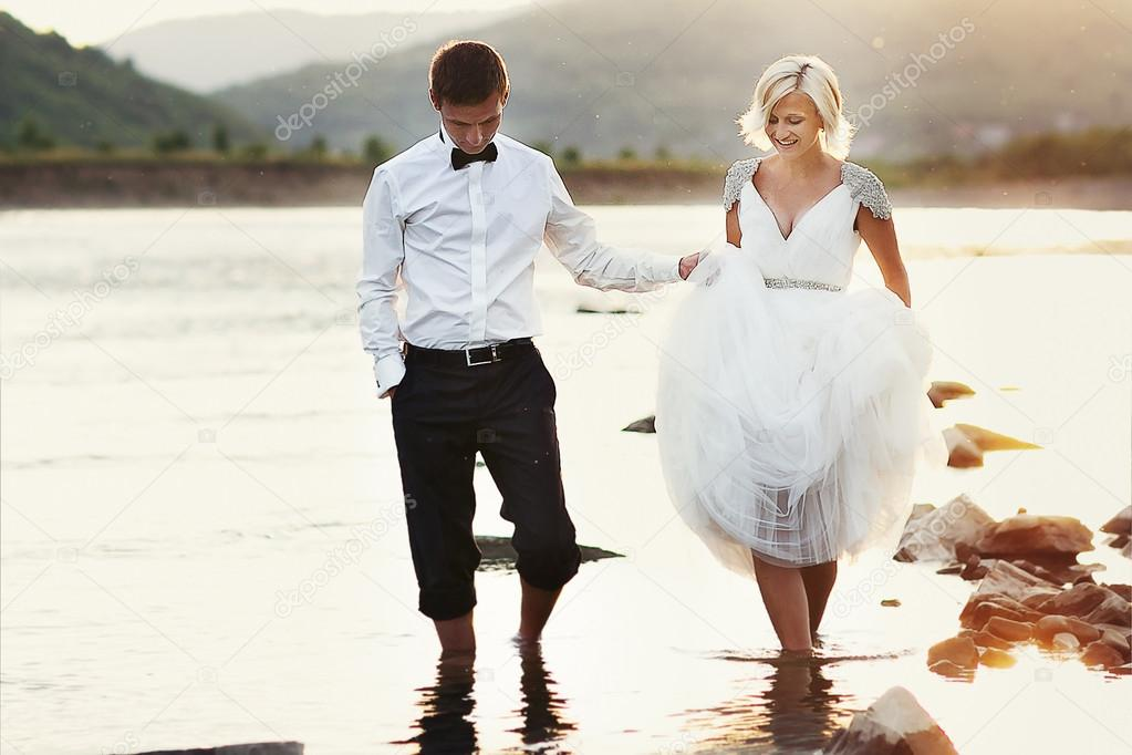 bride and groom walking near the river at sunset