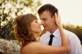 portrét nevěsta a ženich líbat na pozadí paprsky