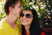 Fotografia coppia sorridente che abbraccia fuori tra i cespugli, in una giornata di sole