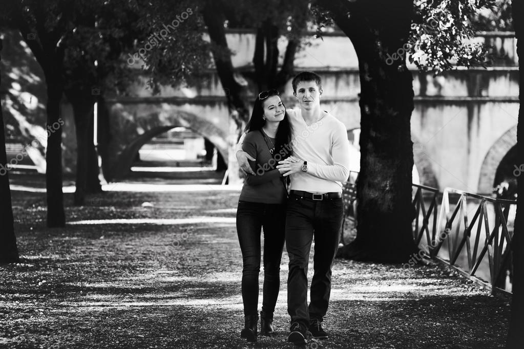 young couple walking in the park among the trees
