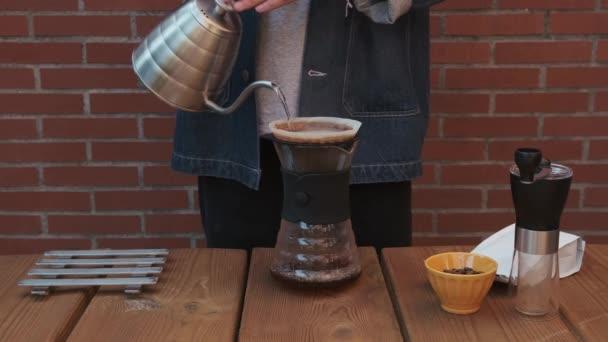 Barista forró vizet önt egy Hario V60-as kancsóba, hogy szűrő kávét főzzön. Közelről..