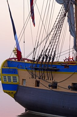 Close up of Hermione frigate stern windows, cannon fodder and the sun on her helm