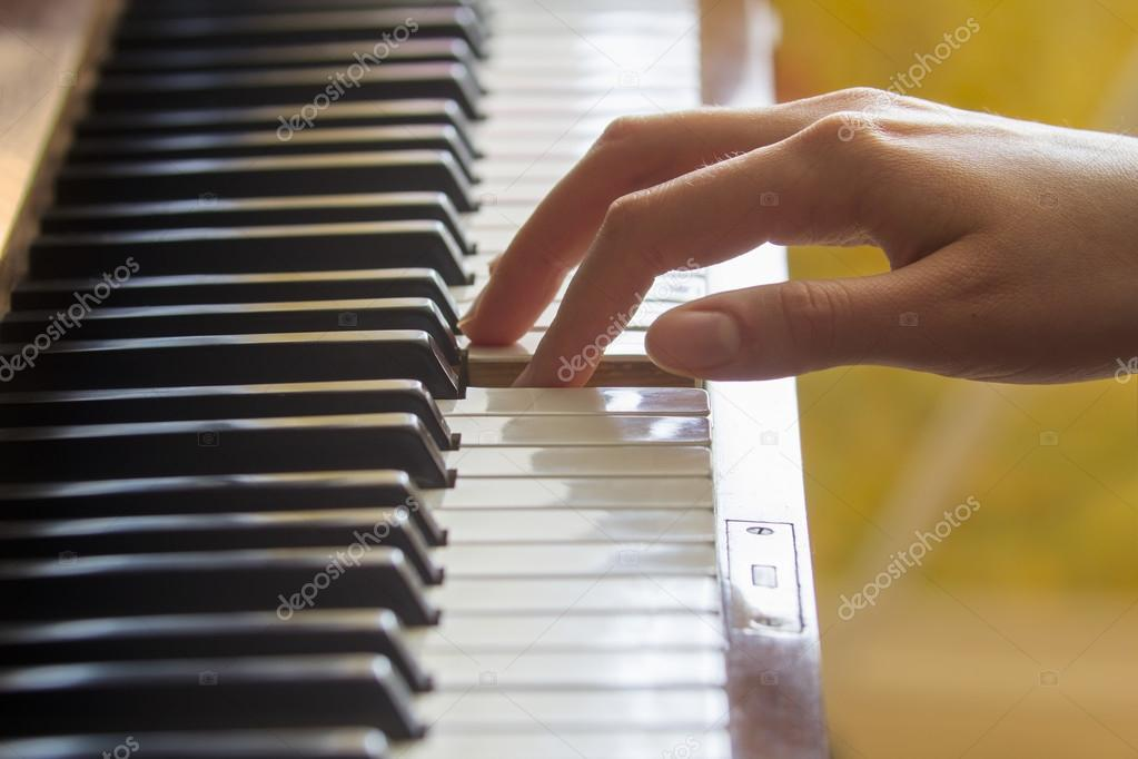 Girl's right hand's finger holding pressed A note key on a