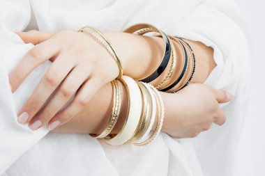 Girl hands with golden bracelets