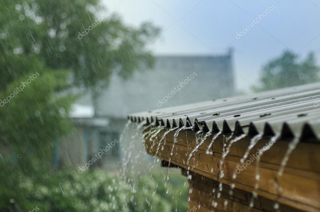 heavy rain flows down from a roof