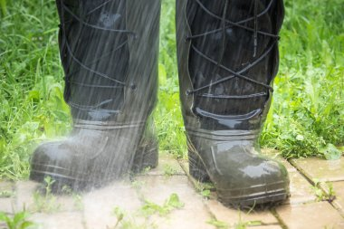 With rubber boots throught the puddle splashing water