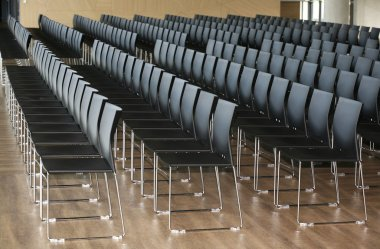 Rows of empty chairs prepared for an indoor event