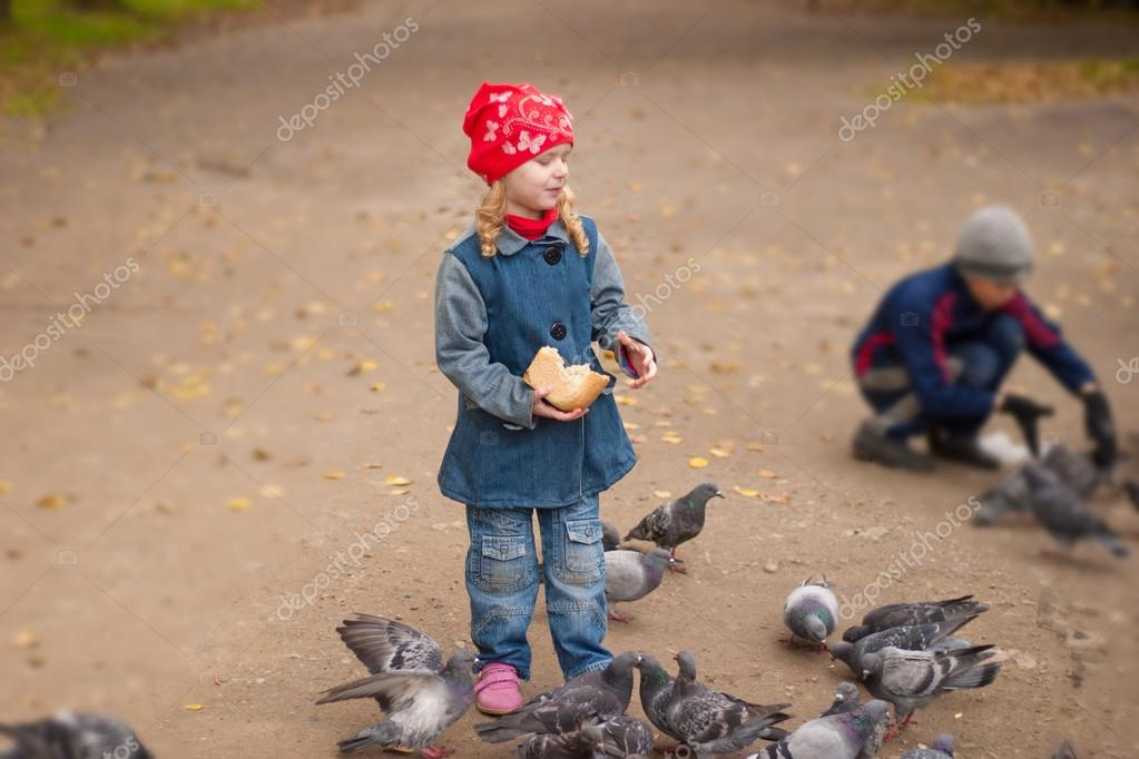 boy and girl feeding pigeons