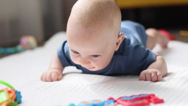 kojenec ležící na břiše na podlaze a usmívající se na hračky