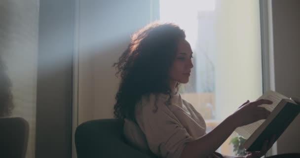 Light shining on a women reading a book