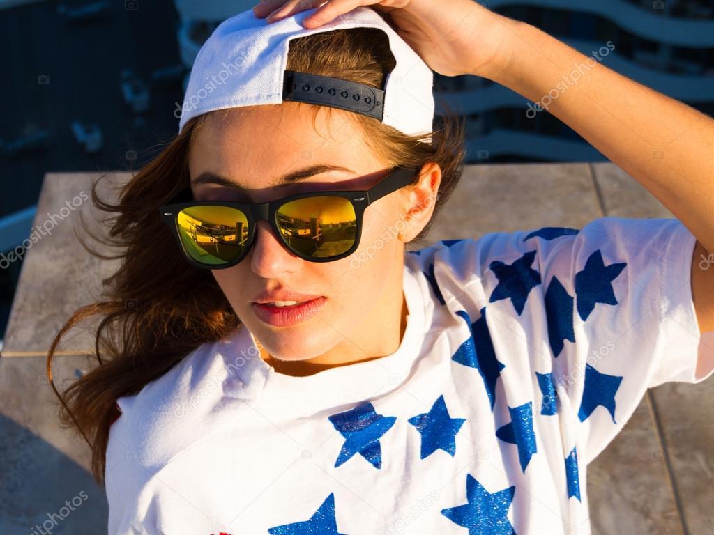 Jeune femme sexy posant dans le toit, portant américain drapeau impression  t-shirt, chapeau blanc swag en miroir lunettes de soleil et maquillage  naturel, ... adac11652b11