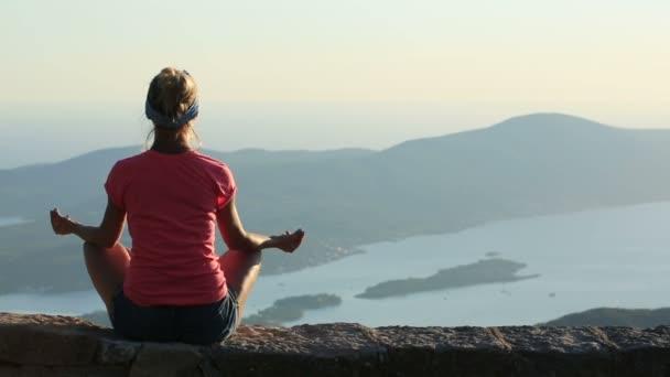 Frau, die auf einem Felsen in den Bergen meditieren