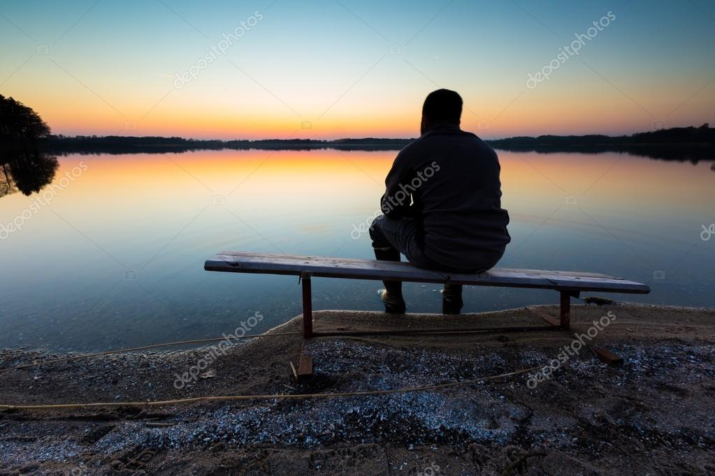 Man sitting on bench on lake shore at sunset