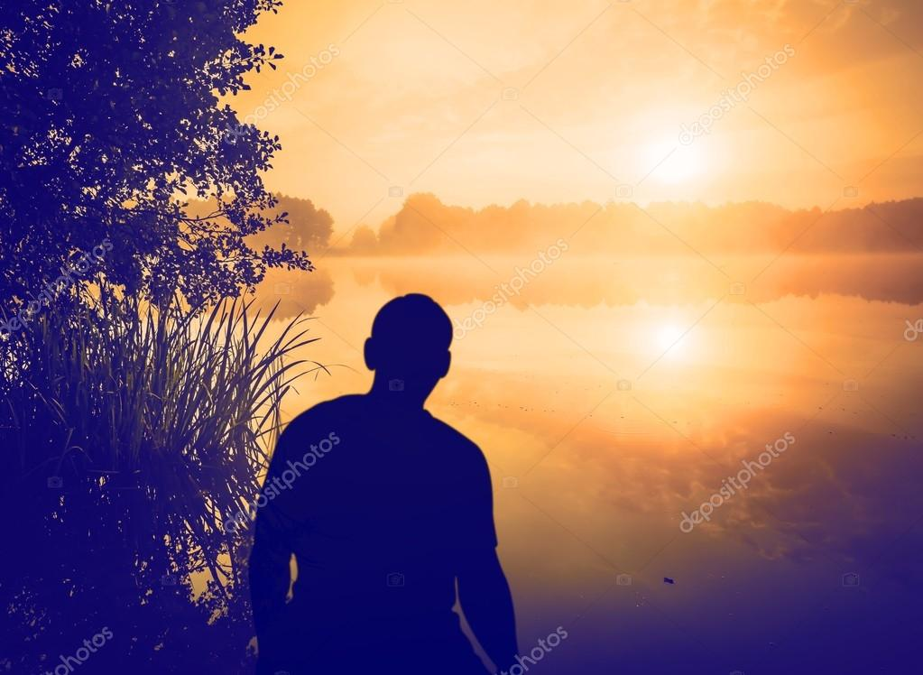 Man watching a sunrise over lake. Human silhouette.