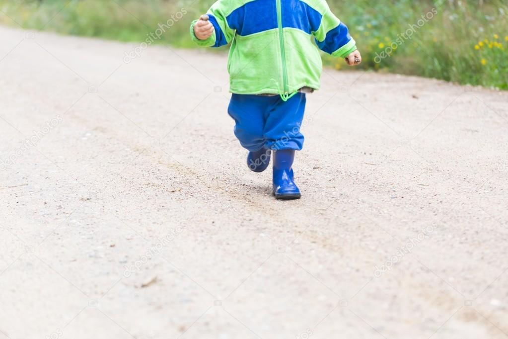 Toddler running by sandy road