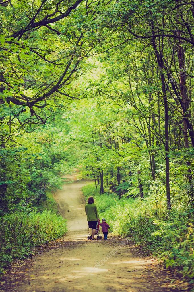 Vintage photo of mother with stroller and baby walking by summer forest path