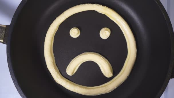 Hurt emoticon made from butter. Accelerated video, butter melts in a skillet