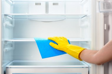 Woman's hand in yellow glove cleaning refrigerator with blue rag