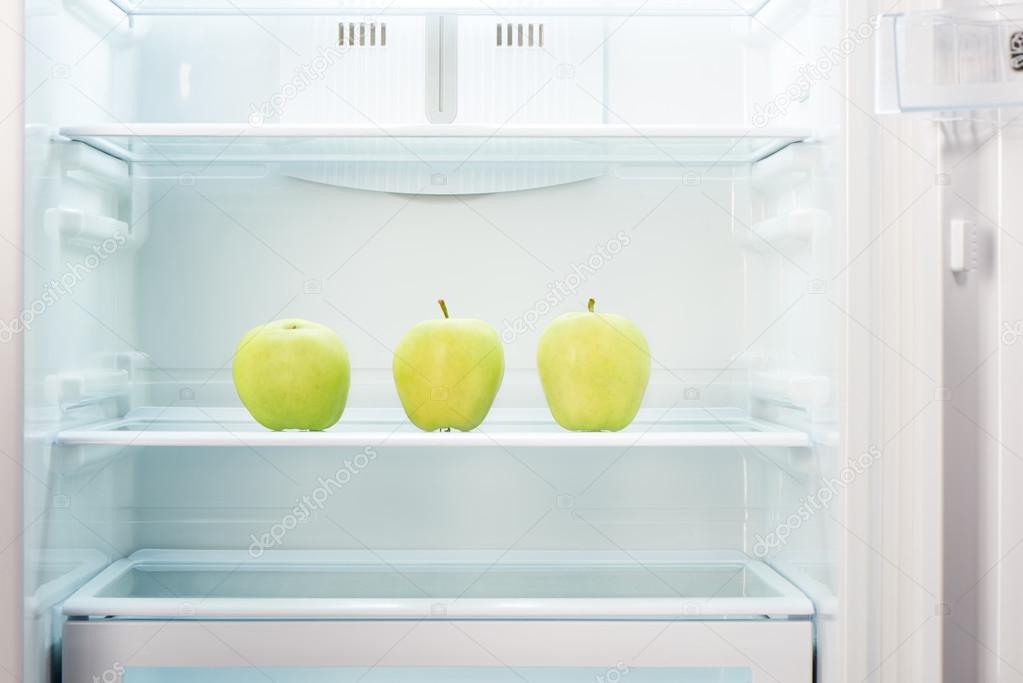 Kühlschrank Regal : Drei grüne Äpfel auf dem regal der offenen leere kühlschrank