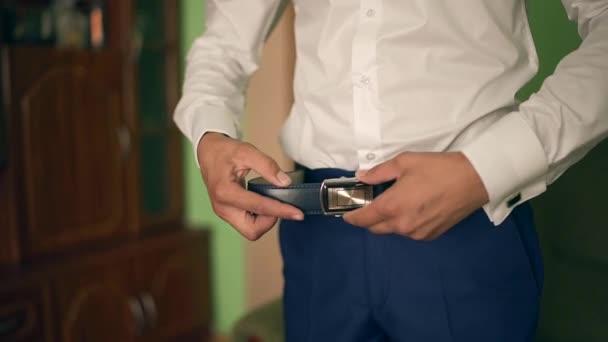 ベルトに入れての実業家。男は、茶色のベルトに置きます。バックルに焦点を当てます。新郎は結婚式のスーツ、ベルトに手を繋いでいます。