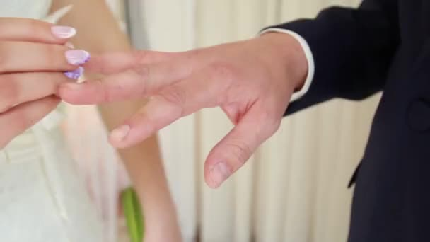 grooms hand putting a wedding ring on the brides finger