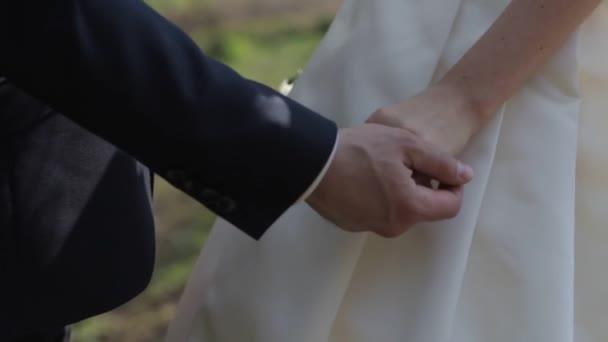 Jemně spojených rukou novomanželé s snubní prsteny na prst na pozadí bílé svatební šaty