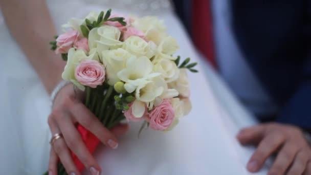ruce nevěsty a ženicha s kroužky na krásné svatební kytice