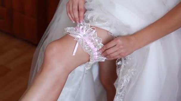nevěsta obléká podvazky na noze. Obrázek krásné ženské bosý nohy ve svatebních šatech. nevěsta obléká punčochy na nohy. nevěsta dávat svatební podvazek na noze