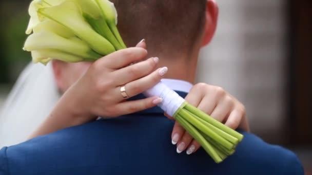 nevěsta objetí ženicha s květinami v rukou
