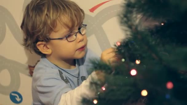 Junge schmückt Weihnachtsspielzeug Weihnachtsbaum