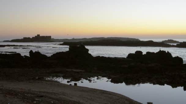 Zobrazit na oceán a krásná silueta skal při západu slunce