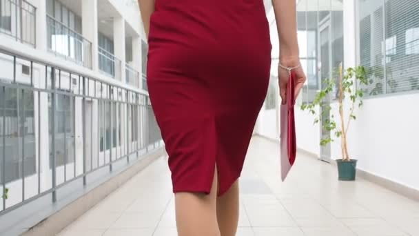 Business woman walks in a business center. View from back