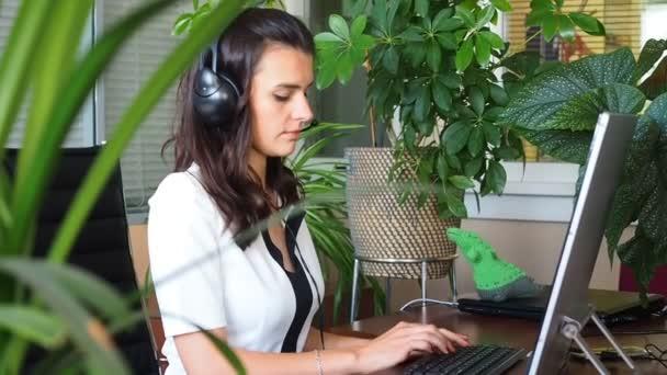 Žena hovoří na sluchátka v úřadu s klientem obklopenou rostlinami